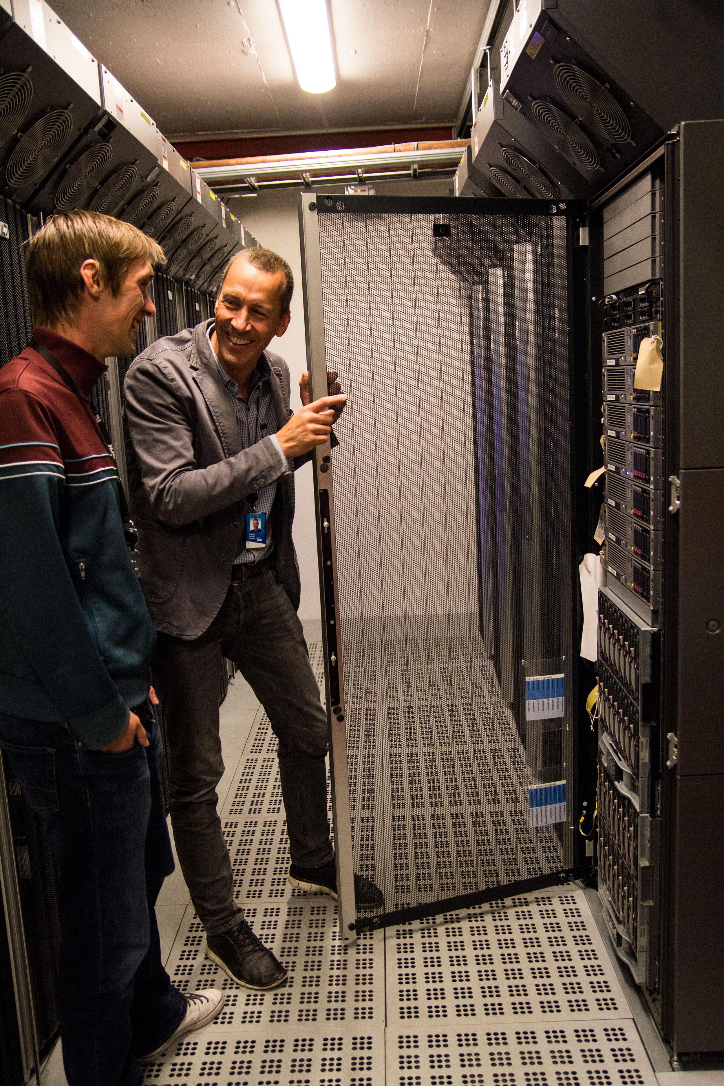 Sverre Reiten, utviklingssjef i Teknologidivisjonen til NRK, holder døren til serverskapet åpen. Ole Andreas Johnsen, prosjektleder i Teknologidivisjonen, følger med.