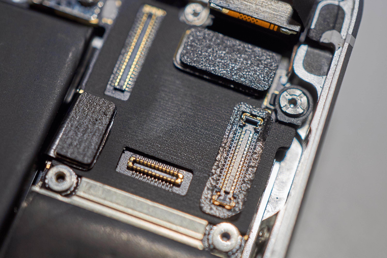 Skjermkontaktene til iPhone SE. Legg merke til tettingen rundt to av kontaktene.